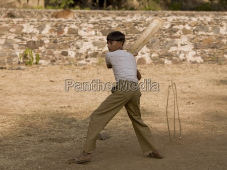 boy playing cricket using makeshift equipment
