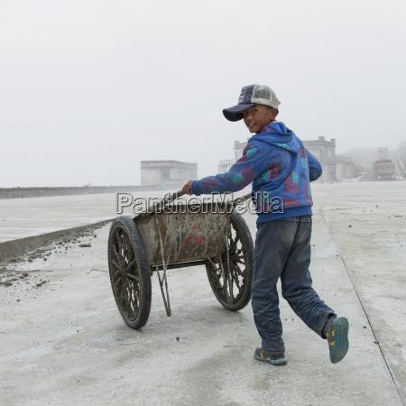 boy pushing two wheeled cart down