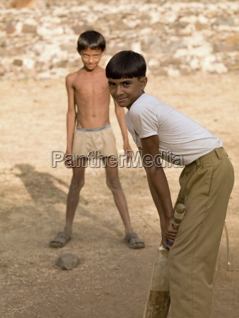 two boys playing cricket using makeshift