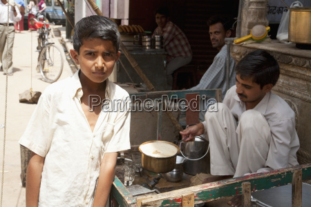 boy standing by a man cooking