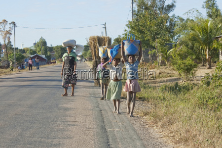 girls carrying bags on their heads