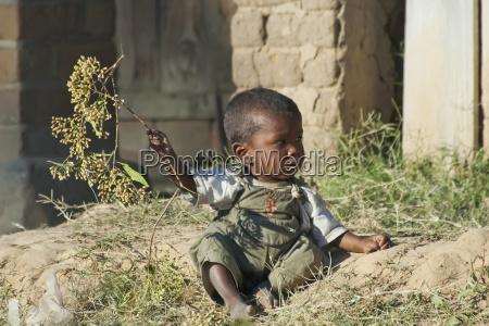 kleiner, junge, der, mit, einem, baumast, in - 25489830