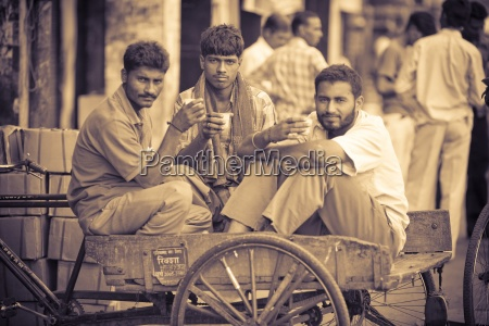 men sharing a drink while sitting