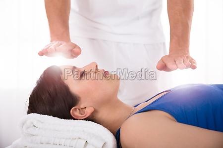 frau die reiki heilende behandlung hat