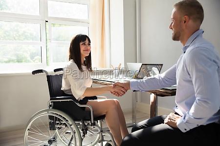 behinderte, geschäftsfrau, schüttelt, hand, mit, ihrem - 25499910