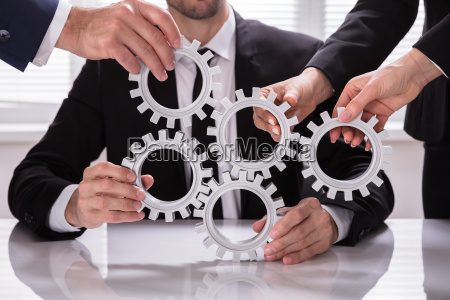 group of businesspeople stacking gears