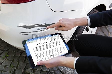 person die beschaedigtes auto beim fuellen