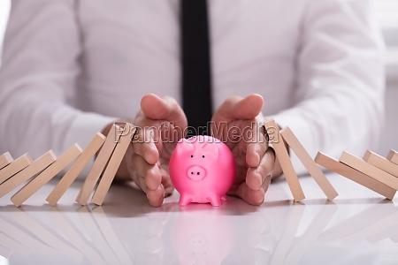 menschliche hand die piggybank vor fallenden