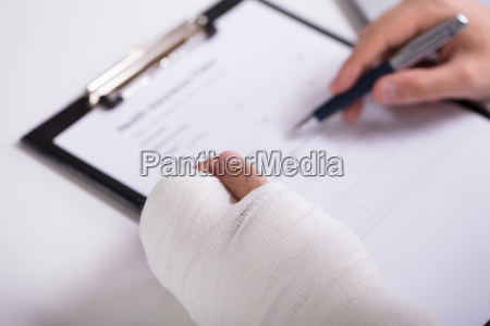 person with fractured hand filling health