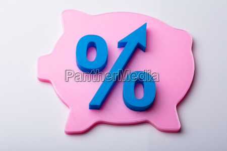 blue percentage symbol over pink piggybank