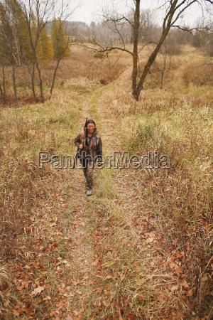 bear hunter walks along logging trail