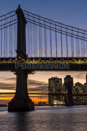 sunset behind manhattan and brooklyn bridges