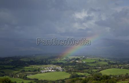 a rainbow over lush fields under