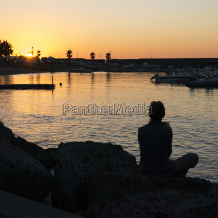 silhouette of a woman sitting at