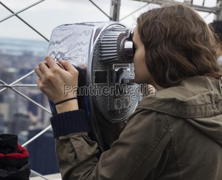 a young woman looks through binoculars