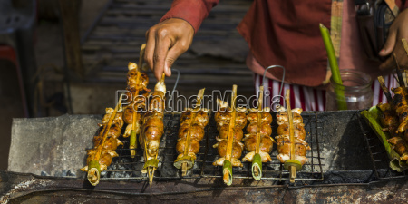 a hand turns skewers on a