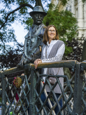 a woman stands beside the monument