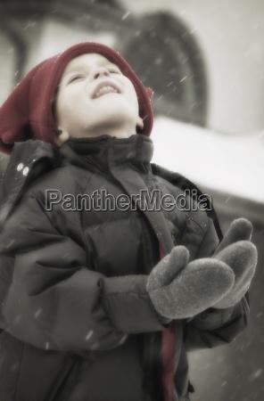 kind geniesst das fangen von schneeflocken