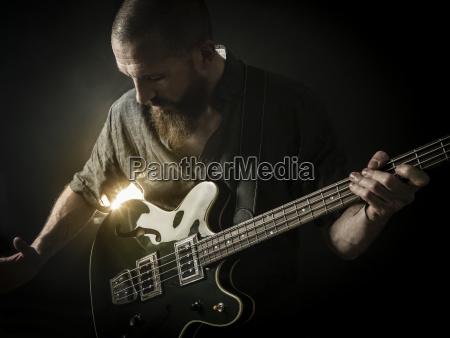bearded man playing bass guitar