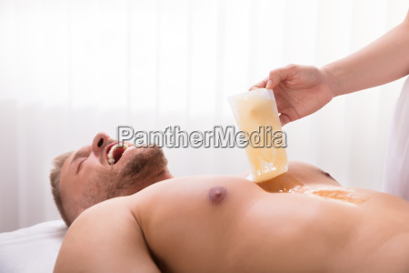 beautician waxing mans chest
