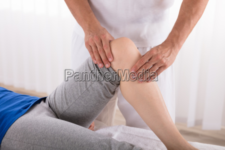 physiotherapeut gibt knie UEbung zu frau