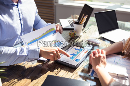 two businesspeople analyzing graph on digital