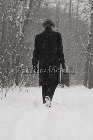 man in dress coat walking through