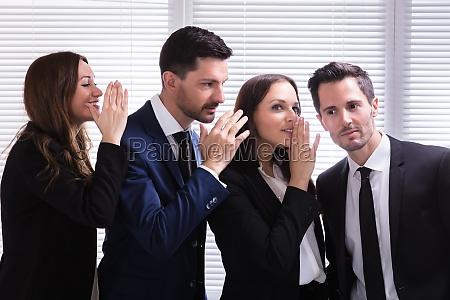 geschaeftsleute gossiping ins ohr des jungen
