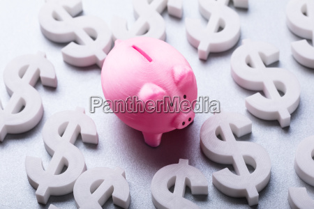 pink piggybank surrounded by many euro