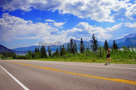 a woman runs along the roadside