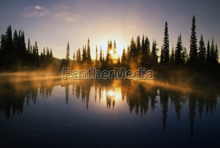 sunbeams through mist over pond