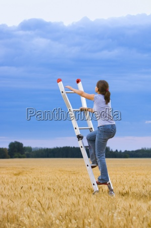 young woman climbing ladder to the