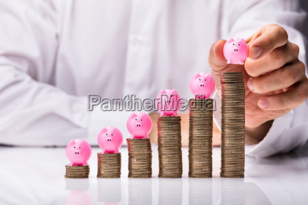 person placing piggybank on increasing stacked