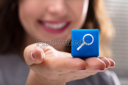 woman holding cubic block with magnifying