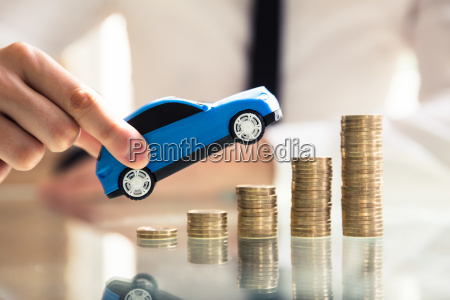 person holding car over rising stacked