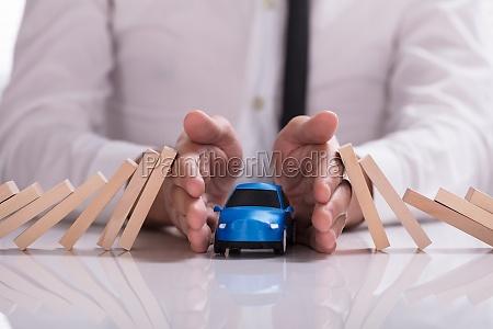 geschaeftsmann der blaues auto vor fallenden