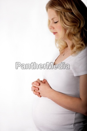 pregnant woman clasping her hands above