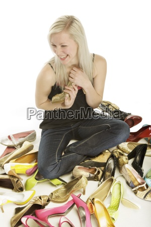 woman holding high heel shoe while