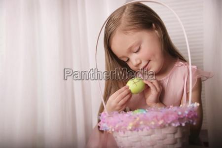 girl holding easter egg with cross