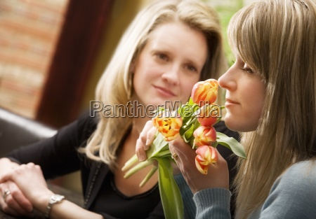 a woman smelling flowers with another