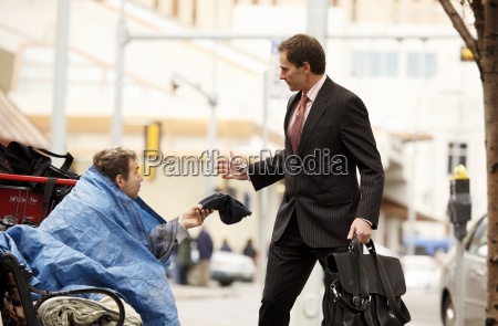 homeless man begging from businessman