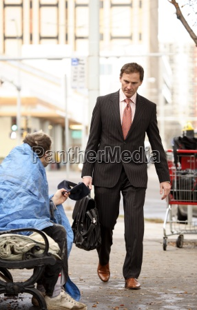 businessman walking by homeless man