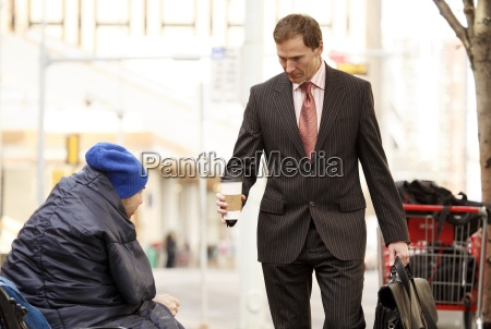 businessman giving coffee to homeless man