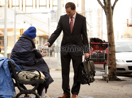 businessman giving food to homeless man