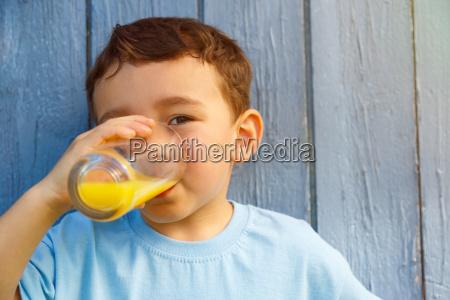 kind kleiner junge trinkt orangensaft saft