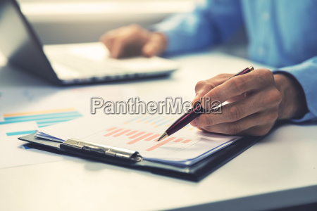 businessman pointing with pen on annual