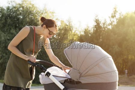 mutter arrangiert moskitonetz auf babywagen sorge