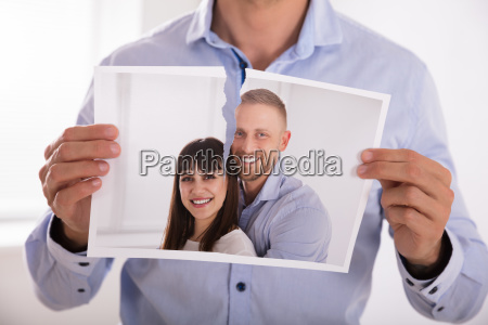 man tearing photo of smiling couple