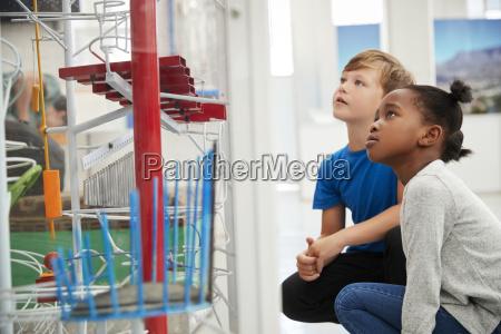 zwei kinder knieten und schauen sich