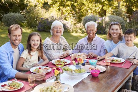dreiergeneration familie beim mittagessen im garten